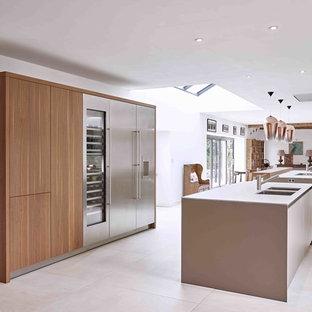デヴォンの大きいトランジショナルスタイルのおしゃれなキッチン (トリプルシンク、フラットパネル扉のキャビネット、茶色いキャビネット、人工大理石カウンター、磁器タイルの床、グレーのキッチンカウンター) の写真