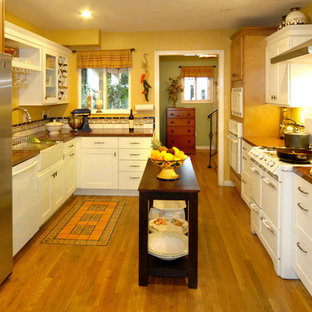 Mediterranean eat-in kitchen designs - Inspiration for a mediterranean galley medium tone wood floor eat-in kitchen remodel in Los Angeles with a farmhouse sink, shaker cabinets, white cabinets, granite countertops, multicolored backsplash, ceramic backsplash and white appliances
