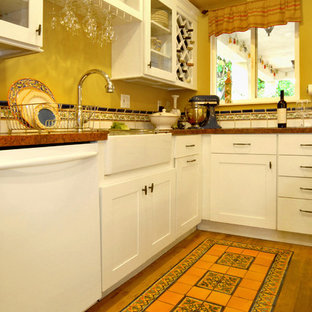 Traditional eat-in kitchen remodeling - Inspiration for a timeless galley ceramic floor eat-in kitchen remodel in Los Angeles with a farmhouse sink, shaker cabinets, white cabinets, granite countertops, multicolored backsplash, ceramic backsplash and white appliances