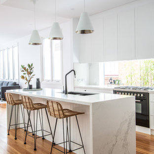 This is an example of a contemporary eat-in kitchen in Sydney with a double-bowl sink, shaker cabinets, white cabinets, quartz benchtops, window splashback, black appliances, light hardwood floors, multiple islands and multi-coloured benchtop.