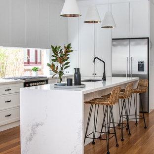 Idéer för att renovera ett funkis vit vitt kök, med vita skåp, bänkskiva i kvarts, fönster som stänkskydd, en undermonterad diskho, luckor med infälld panel, rostfria vitvaror, mellanmörkt trägolv, en köksö och brunt golv