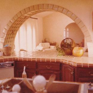 Inredning av ett medelhavsstil stort kök, med en trippel diskho, luckor med upphöjd panel, skåp i mörkt trä, kaklad bänkskiva, beige stänkskydd, stänkskydd i terrakottakakel, integrerade vitvaror, klinkergolv i terrakotta och en köksö