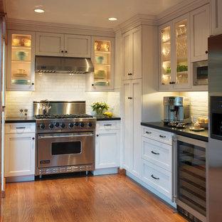 Immagine di una cucina a L chic chiusa con paraspruzzi con piastrelle diamantate, elettrodomestici in acciaio inossidabile, ante di vetro, ante bianche e paraspruzzi bianco