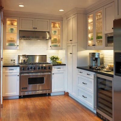 Inspiration for a timeless u-shaped enclosed kitchen remodel in San Francisco with subway tile backsplash, stainless steel appliances, white cabinets, white backsplash and recessed-panel cabinets