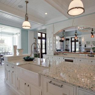 Idéer för ett stort klassiskt linjärt kök och matrum, med en rustik diskho, luckor med glaspanel, vita skåp, bänkskiva i återvunnet glas, integrerade vitvaror, klinkergolv i keramik och en köksö