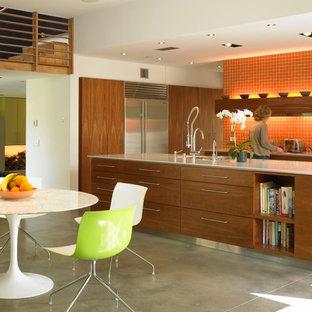 Foto di una cucina moderna con lavello sottopiano, ante lisce, ante in legno scuro, paraspruzzi arancione, elettrodomestici in acciaio inossidabile e pavimento in cemento
