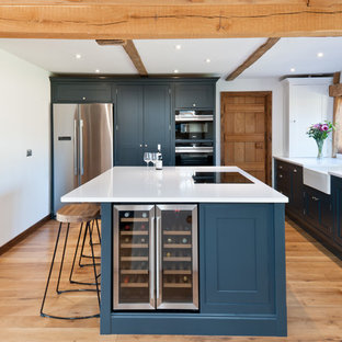 Medium sized farmhouse l-shaped enclosed kitchen in Kent with a belfast sink, blue cabinets, quartz worktops, stainless steel appliances, light hardwood flooring, an island, beige floors, white worktops and shaker cabinets.