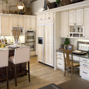 Large traditional enclosed kitchen designs - Enclosed kitchen - large traditional single-wall medium tone wood floor and brown floor enclosed kitchen idea in Miami with a farmhouse sink, raised-panel cabinets, distressed cabinets, granite countertops, brown backsplash, travertine backsplash, paneled appliances and an island