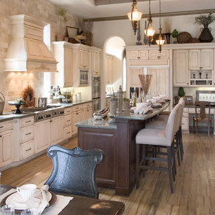 Large traditional enclosed kitchen inspiration - Example of a large classic single-wall medium tone wood floor and brown floor enclosed kitchen design in Miami with paneled appliances, a farmhouse sink, raised-panel cabinets, distressed cabinets, granite countertops, brown backsplash, travertine backsplash and an island