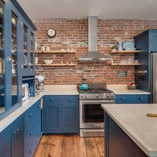Klassische Küche in L-Form mit Glasfronten, blauen Schränken, Rückwand aus Backstein, Küchengeräten aus Edelstahl, braunem Holzboden und Kücheninsel in Portland Maine