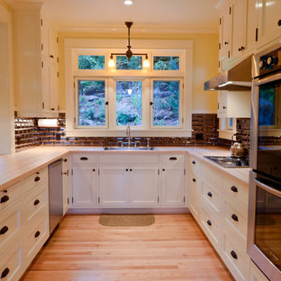 Design ideas for a traditional u-shaped kitchen in Portland with wood benchtops, a drop-in sink, shaker cabinets, white cabinets, black splashback, subway tile splashback and stainless steel appliances.