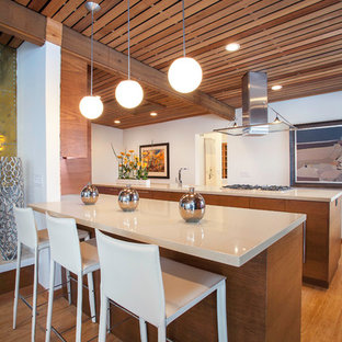 Midcentury kitchen in Salt Lake City with flat-panel cabinets, medium wood cabinets, medium hardwood floors, a peninsula and beige benchtop.