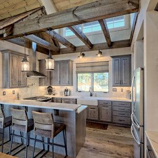 他の地域の小さいカントリー風おしゃれなキッチン (エプロンフロントシンク、レイズドパネル扉のキャビネット、クオーツストーンカウンター、白いキッチンパネル、トラバーチンのキッチンパネル、シルバーの調理設備、茶色い床、白いキッチンカウンター、グレーのキャビネット、無垢フローリング) の写真