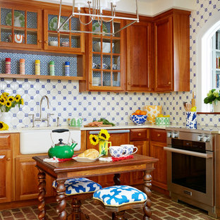 Design ideas for a country u-shaped separate kitchen in DC Metro with a farmhouse sink, medium wood cabinets, blue splashback, ceramic splashback, stainless steel appliances, brick floors, with island, raised-panel cabinets and brown floor.