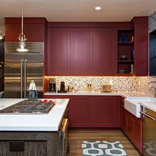 ソルトレイクシティの中くらいのトランジショナルスタイルのおしゃれなキッチン (エプロンフロントシンク、珪岩カウンター、シルバーの調理設備、無垢フローリング、シェーカースタイル扉のキャビネット、赤いキャビネット、マルチカラーのキッチンパネル、ガラスタイルのキッチンパネル、茶色い床) の写真