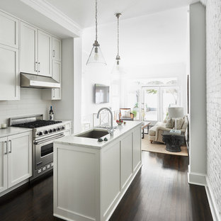Traditional kitchen designs - Kitchen - traditional galley dark wood floor kitchen idea in DC Metro with shaker cabinets, white cabinets, white backsplash, subway tile backsplash and an island