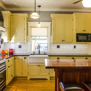 オレンジカウンティの中サイズのカントリー風おしゃれなキッチン (エプロンフロントシンク、シェーカースタイル扉のキャビネット、黄色いキャビネット、御影石カウンター、白いキッチンパネル、磁器タイルのキッチンパネル、無垢フローリング) の写真
