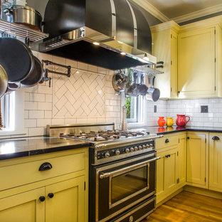 Idee per una cucina chic di medie dimensioni con lavello stile country, ante in stile shaker, ante gialle, top in saponaria, paraspruzzi bianco, paraspruzzi con piastrelle in ceramica, elettrodomestici neri e pavimento in legno massello medio