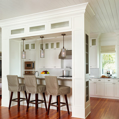 Kitchen - tropical kitchen idea in Charleston with shaker cabinets, stainless steel appliances, white cabinets and white backsplash