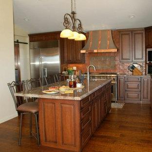 Mittelgroße Klassische Wohnküche in L-Form mit profilierten Schrankfronten, hellbraunen Holzschränken, Granit-Arbeitsplatte, Küchenrückwand in Orange, Rückwand aus Porzellanfliesen, Küchengeräten aus Edelstahl, braunem Holzboden und Kücheninsel in Santa Barbara