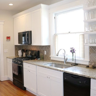 Photo of a small traditional galley eat-in kitchen in New York with an undermount sink, shaker cabinets, white cabinets, granite benchtops, grey splashback, glass tile splashback, medium hardwood floors, a peninsula, stainless steel appliances, brown floor and beige benchtop.