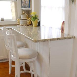 ニューヨークの小さいシャビーシック調のおしゃれなキッチン (アンダーカウンターシンク、シェーカースタイル扉のキャビネット、白いキャビネット、御影石カウンター、グレーのキッチンパネル、ガラスタイルのキッチンパネル、無垢フローリング、シルバーの調理設備の、茶色い床、ベージュのキッチンカウンター) の写真