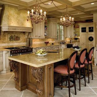 Photo of a large mediterranean u-shaped kitchen in Santa Barbara with a farmhouse sink, raised-panel cabinets, light wood cabinets, beige splashback, with island, limestone benchtops, limestone floors, beige floor and limestone splashback.