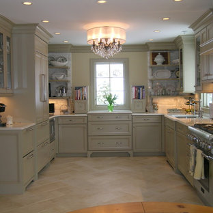 Enclosed kitchen - traditional travertine floor enclosed kitchen idea in Newark with paneled appliances, an undermount sink, recessed-panel cabinets, green cabinets, quartz countertops, white backsplash and stone tile backsplash