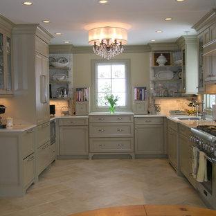 Modelo de cocina clásica, cerrada, con electrodomésticos con paneles, fregadero bajoencimera, armarios con paneles empotrados, puertas de armario verdes, encimera de cuarzo compacto, salpicadero blanco, salpicadero de azulejos de piedra y suelo de travertino
