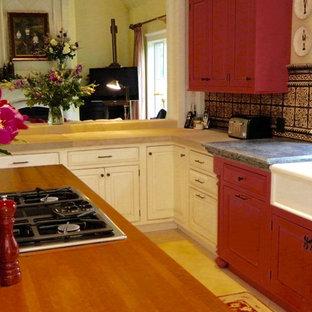 Inredning av ett klassiskt avskilt, stort l-kök, med en rustik diskho, luckor med profilerade fronter, röda skåp, bänkskiva i täljsten, flerfärgad stänkskydd, stänkskydd i terrakottakakel, integrerade vitvaror, kalkstensgolv och en köksö