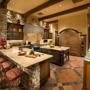 フェニックスの広い地中海スタイルのおしゃれなキッチン (ドロップインシンク、中間色木目調キャビネット、大理石カウンター、ベージュキッチンパネル、セラミックタイルのキッチンパネル、パネルと同色の調理設備、セラミックタイルの床、赤い床) の写真