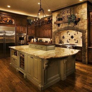 オーランドの大きいヴィクトリアン調のおしゃれなキッチン (エプロンフロントシンク、レイズドパネル扉のキャビネット、緑のキャビネット、御影石カウンター、ベージュキッチンパネル、石タイルのキッチンパネル、シルバーの調理設備の、濃色無垢フローリング、茶色い床) の写真
