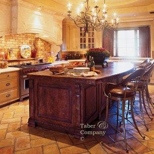 フェニックスの大きい地中海スタイルのおしゃれなアイランドキッチン (エプロンフロントシンク、ヴィンテージ仕上げキャビネット、木材カウンター、セメントタイルのキッチンパネル、レンガの床) の写真