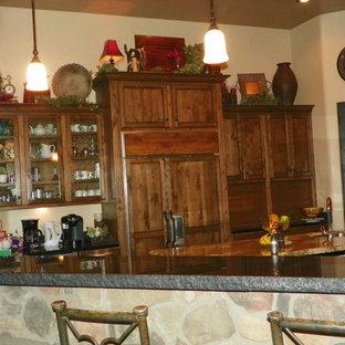 Große Mediterrane Wohnküche in U-Form mit Triple-Waschtisch, profilierten Schrankfronten, Schränken im Used-Look, Granit-Arbeitsplatte, Küchenrückwand in Braun, Rückwand aus Stein, Küchengeräten aus Edelstahl, Travertin und zwei Kücheninseln in Phoenix