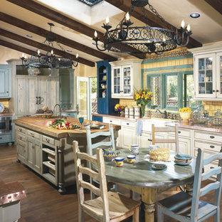 Große Klassische Wohnküche in U-Form mit Einbauwaschbecken, profilierten Schrankfronten, weißen Schränken, Kupfer-Arbeitsplatte, Küchenrückwand in Gelb, Rückwand aus Keramikfliesen, bunten Elektrogeräten, dunklem Holzboden, Kücheninsel und braunem Boden in Los Angeles