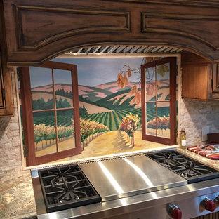 サンフランシスコの大きい地中海スタイルのおしゃれなアイランドキッチン (エプロンフロントシンク、レイズドパネル扉のキャビネット、ヴィンテージ仕上げキャビネット、御影石カウンター、ベージュキッチンパネル、石タイルのキッチンパネル、シルバーの調理設備の、リノリウムの床) の写真