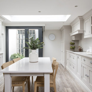 This is an example of a medium sized classic galley kitchen/diner in London with a submerged sink, shaker cabinets, grey cabinets, white splashback, integrated appliances, no island, grey floors and white worktops.