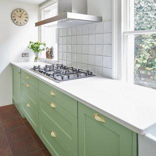 ロンドンの小さいエクレクティックスタイルのおしゃれなII型キッチン (エプロンフロントシンク、シェーカースタイル扉のキャビネット、緑のキャビネット、珪岩カウンター、白いキッチンパネル、セラミックタイルのキッチンパネル、パネルと同色の調理設備、テラコッタタイルの床) の写真