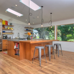 This is an example of a midcentury galley kitchen in San Francisco with open cabinets, medium wood cabinets, grey splashback and stainless steel appliances.