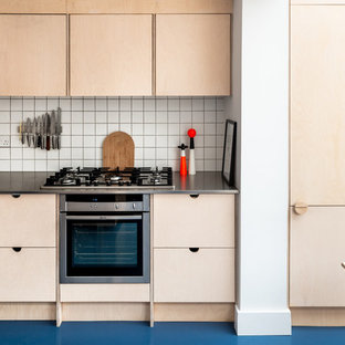 This is an example of a scandinavian kitchen in London with light wood cabinets, stainless steel benchtops, blue floor, flat-panel cabinets, white splashback and stainless steel appliances.