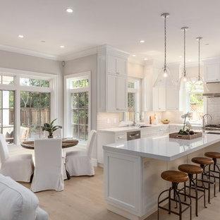 Bild på ett vintage kök, med en undermonterad diskho, luckor med infälld panel, vita skåp, vitt stänkskydd, rostfria vitvaror, ljust trägolv, en köksö och beiget golv
