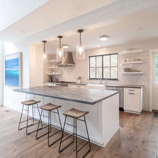 サンタバーバラの中くらいのトランジショナルスタイルのおしゃれなキッチン (無垢フローリング、茶色い床、塗装板張りの天井、エプロンフロントシンク、シェーカースタイル扉のキャビネット、白いキャビネット、白いキッチンパネル、シルバーの調理設備、グレーのキッチンカウンター) の写真