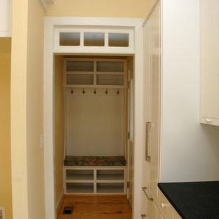 ローリーの小さいカントリー風おしゃれなキッチン (エプロンフロントシンク、インセット扉のキャビネット、白いキャビネット、御影石カウンター、黄色いキッチンパネル、シルバーの調理設備の、淡色無垢フローリング) の写真