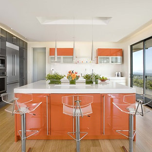 Example of a trendy bamboo floor kitchen design in San Francisco with stainless steel appliances, flat-panel cabinets and orange cabinets