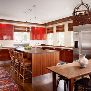 Photo of a mediterranean l-shaped kitchen/diner in Austin with flat-panel cabinets, dark hardwood flooring, an island, brown floors, red cabinets and grey worktops.