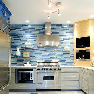 Idéer för funkis kök, med rostfria vitvaror, blått stänkskydd och stänkskydd i stickkakel