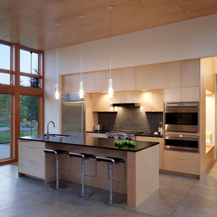 This is an example of a modern galley kitchen in Seattle with flat-panel cabinets, light wood cabinets, black splashback, stainless steel appliances and slate splashback.