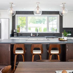 На фото: параллельная кухня в стиле неоклассика (современная классика) с обеденным столом, врезной раковиной, белыми фасадами, столешницей из талькохлорита, черным фартуком, фартуком из плитки мозаики, техникой из нержавеющей стали, островом, черной столешницей, фасадами в стиле шейкер, темным паркетным полом и коричневым полом с
