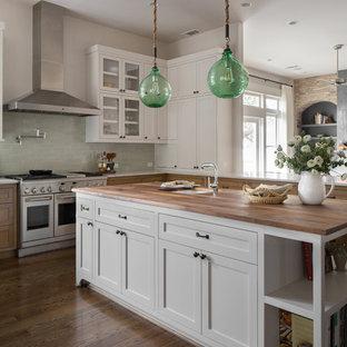 Bild på ett vintage brun brunt kök, med skåp i shakerstil, grönt stänkskydd, stänkskydd i keramik, rostfria vitvaror, en köksö, vita skåp, träbänkskiva, mörkt trägolv och brunt golv