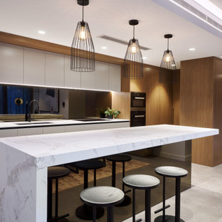 Inspiration for a large contemporary l-shaped kitchen in Perth with an undermount sink, flat-panel cabinets, white cabinets, black splashback, glass sheet splashback, panelled appliances, with island, grey floor and white benchtop.